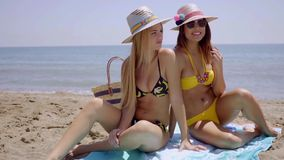 Two sexy flirtatious young women. Sitting on a towel on the beach in their bikinis looking provocatively at the camera with happy smiles stock video