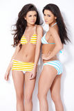 Two sexy girl in colorful swimsuits. Posing over white background Stock Photos