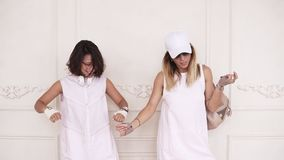 Two girl friends in white dresses dancing off, enjoying spending time together. Indoors footage stock video footage