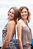 Two girl standing back to back Royalty Free Stock Photo