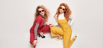 Two Gorgeous Girl in Fashion Outfit. Curly Hair. Two Girl in Trendy Outfit with Curly Hairstyle, makeup. Fashionable Gorgeous Woman in Red Yellow jumpsuit, heels stock photos