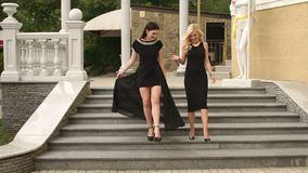 Two sexy girls in black dresses go down the stairs. Two sexy girls in black evening dresses go down the stairs, slow motion stock footage