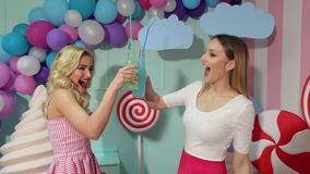 Two funny girls clink bottles with a cocktail. Two sexy girls in bright summer dresses drink juice or a cocktail of glass bottles and tubes against the backdrop stock video footage