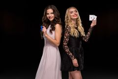 Two girls brunette and blonde, posing with chips and cards in their hands, poker concept black background Royalty Free Stock Images
