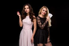 Two girls brunette and blonde, posing with chips in her hands, poker concept black background Stock Images