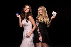 Two girls brunette and blonde, posing with chips in her hands, poker concept black background Royalty Free Stock Image