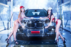 Two sexy girls in car wash. Girls in bathing suits, a car wash by hand with sponge and foam Royalty Free Stock Photography