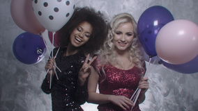 Two sexy girls dancing with colorful balloons in studio. Two beautiful elegant women in evening shiny dresses holding balloons. Two woman at the party stock video