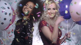 Two sexy girls dancing among colorful confetti in studio. Two beautiful elegant women in evening shiny dresses holding balloons and dancing. Two woman at the stock video footage