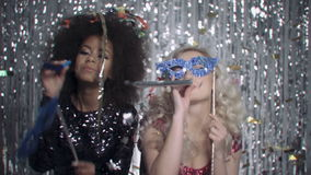 Two sexy girls dancing among colorful confetti in studio. Two beautiful elegant women in evening shiny dresses holding carnival masks and dancing. Two woman at stock footage