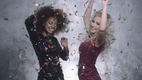 Two sexy girls dancing among shiny silver confetti in studio. stock video footage