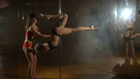 Two sexy girls doing a pole in the gym. stock video