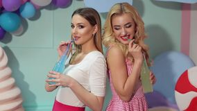 Two sexy girls drink juice of glass bottles. Two sexy girls in bright summer dresses drink juice or a cocktail of glass bottles and tubes against the backdrop stock video