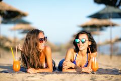 Sexy girls having fun on a beach. Two sexy girls drinking cocktails having fun on a beach Royalty Free Stock Images