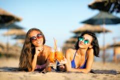Sexy girls having fun on a beach. Two sexy girls drinking cocktails having fun on a beach Royalty Free Stock Photos