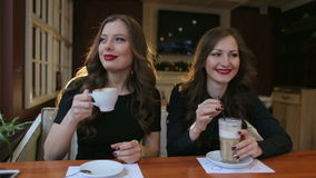 Two sexy girls drinking coffee in cafe, close-up. Two sexy brunettes in black dresses and red lipstick, drinking coffee in cafe, close-up stock video footage