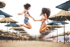 Two sexy girls jumping on a beach Royalty Free Stock Photo
