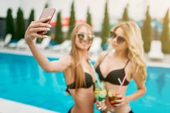 Two sexy girls makes selfie near the swimmimg pool Stock Images