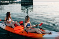 Two girls rest on kayaks in the middle of the sea. Lay down and enjoy the dawn royalty free stock photography