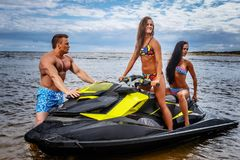 Two sexy girls in swimsuit and shirtless muscular male, have fun with a jet ski on a sea. Two sexy girls in swimsuit and shirtless muscular male, have fun with Stock Images