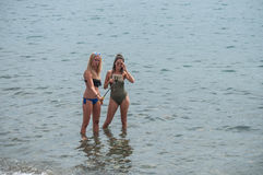 Two girls in swimsuit taking a selfie in the water with smartphone stock photography