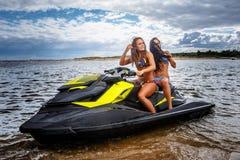 Two sexy girls in a swimwear, sitting on a jet ski, have fun at a leisure. Two sexy girls in a swimwear, sitting on a jet ski, have fun Stock Photos