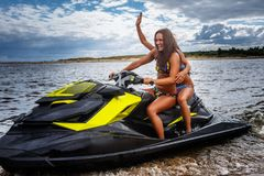 Two sexy girls in a swimwear, sitting on a jet ski, have fun at a leisure. Two sexy girls in a swimwear, sitting on a jet ski, have fun Royalty Free Stock Images