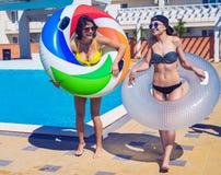 Two girls walking with swimming circles near swimming pool royalty free stock photo