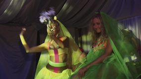 Two sexy go go girls dance in wedding colorful veils, skirts wave artificial bouquets in nightclub stock video footage