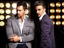Two handsome fashion male models men dressed in elegant suits royalty free stock photo