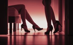 Two sexy ladies in high heels. Women having sex. Lesbians, prostitutes or escorts. Long legs silhouette in red light. Sexual glamour lingerie models. Laying on royalty free stock photography