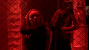 Two ladies standing behind metal chain fence in red light, nightlife. Stock photo royalty free stock photo