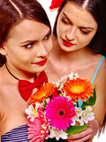 Two sexy lesbian women with flower. Two sexy lesbian women holding flower bouquet. Isolated Stock Photo