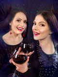Two sexy lesbian women with red wine. Black background Stock Image