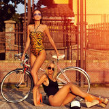Two model girls posing near a vintage bike. Outdoor fashion royalty free stock photography