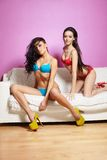 Two sexy models posing on white sofa pink walls Royalty Free Stock Photos