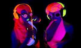 Two sexy neon uv glow dancers. Two sexy female disco dancers posing in UV costume Stock Photo