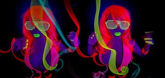 Two sexy neon uv glow dancers. Two sexy female disco dancers posing in UV costume Royalty Free Stock Photos