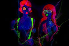Two sexy neon uv glow dancers. Two sexy female disco dancers posing in UV costume Royalty Free Stock Images