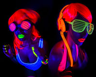 Two sexy neon uv glow dancers. Two sexy female disco dancers posing in UV costume Stock Photography