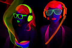Two sexy neon uv glow dancers. Two sexy female disco dancers posing in UV costume Royalty Free Stock Image