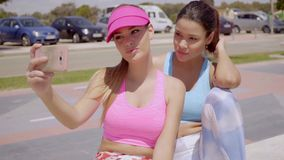 Two sexy sporty young women taking a selfie. On a mobile phone as they sit on a low wall in the summer sunshine stock video