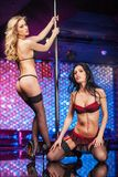 Two sexy striptease dancers posing on stage. Stock Photography