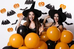 Two sexy posing on a white background in black witch hats and with bundles of ballons in their hands. They are laughing Royalty Free Stock Photos