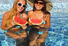 Two sexy women with dark hair eating watermelon. In the pool Stock Photography