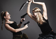 Two women with gun and dagger. On gray stock image