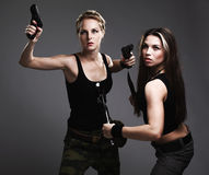 Two sexy women with gun and dagger Royalty Free Stock Images