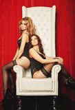 Two sexy women in lingerie on white throne Royalty Free Stock Images