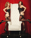 Two sexy women in lingerie on white throne Stock Photos