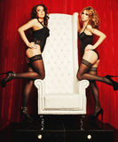 Two sexy women in lingerie on white throne Stock Images